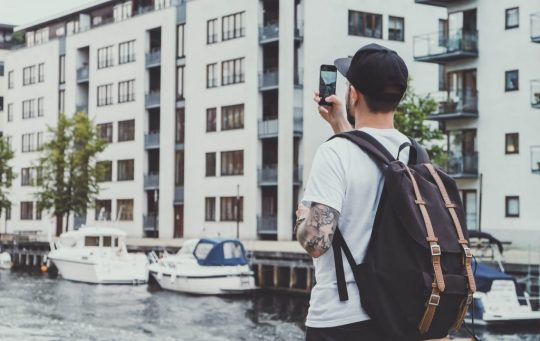 Man taking a picture of some buildings with his phone