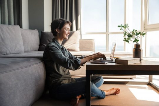 Woman typing on a laptop in front of her couch