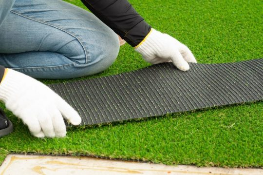 Someone installing artificial grass with white gloves on