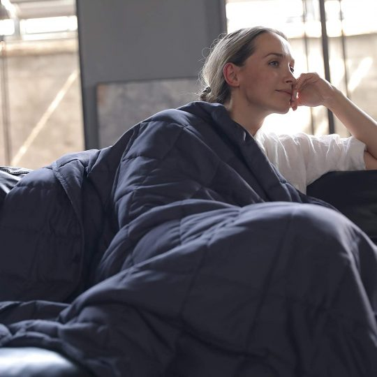 Woman wrapped in a weighted blanket