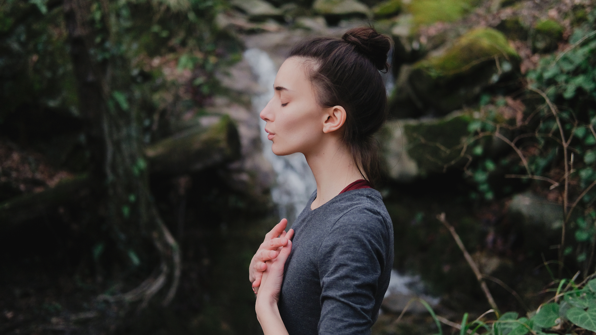 Woman taking a breath with hands on her chest in front of a waterfall