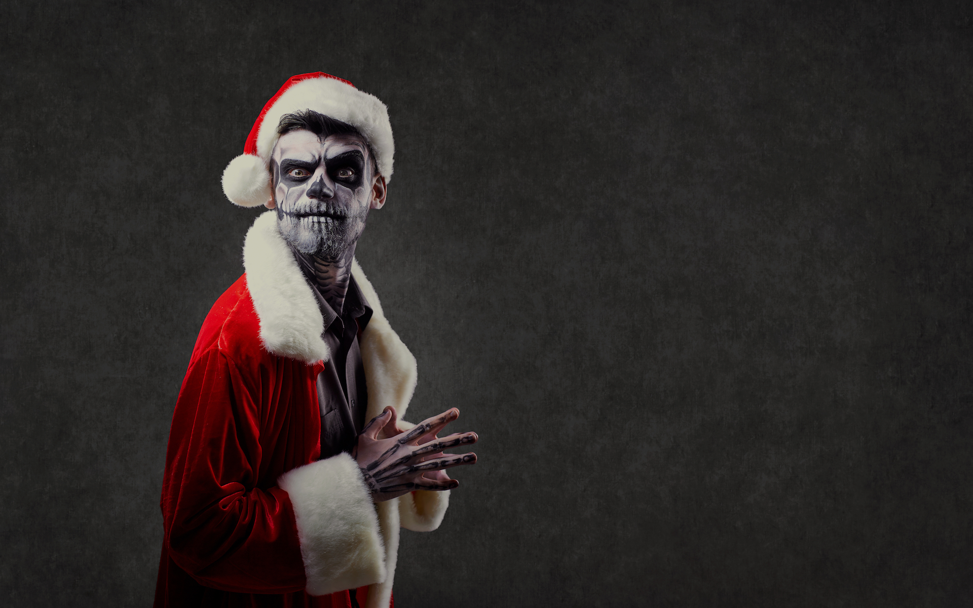 Man with skeleton makeup wearing a Santa suit and looking at the camera