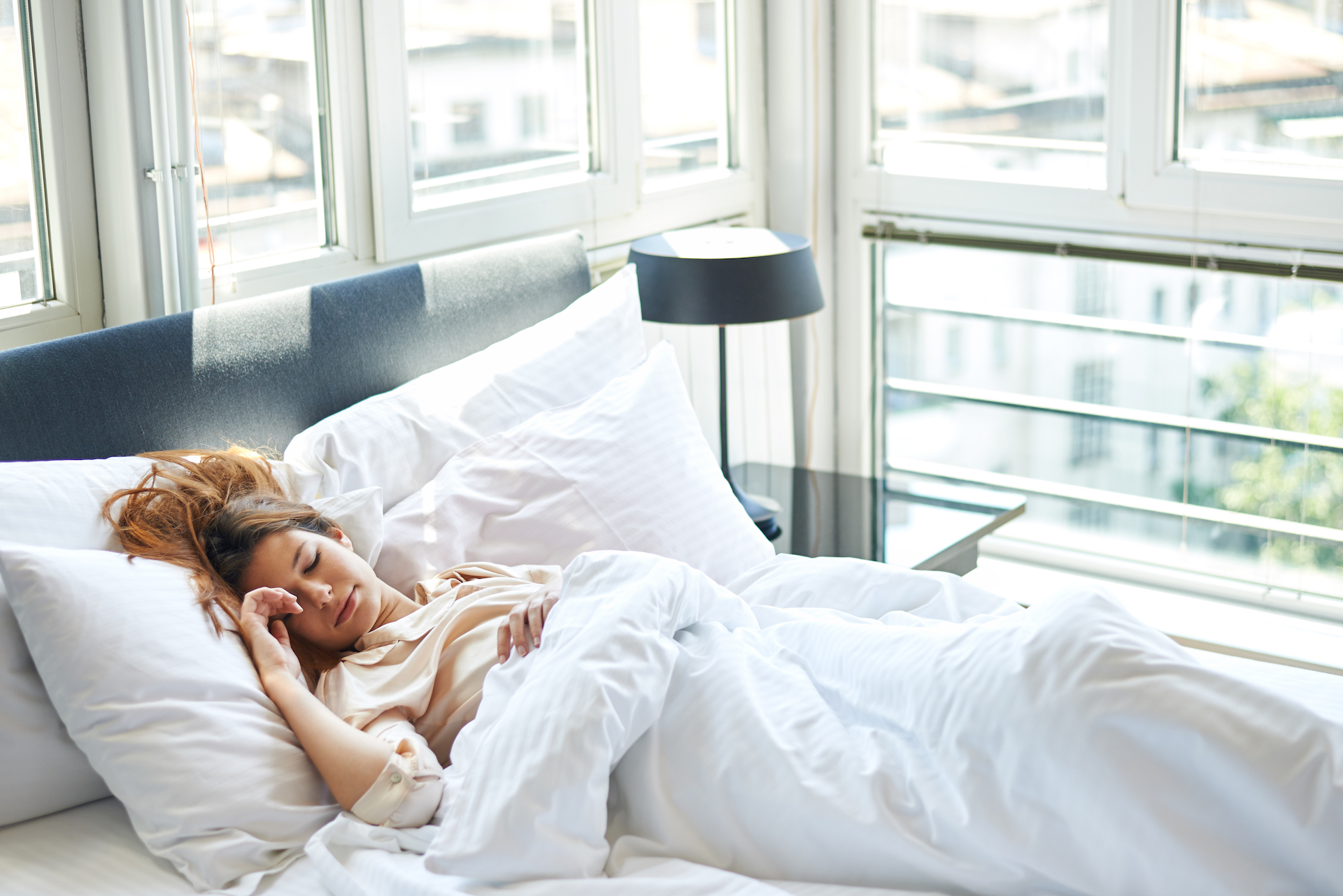 Woman happily sleeping in her bed