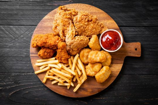 Plate with ketchup, chicken wings, chicken nuggets and french fries
