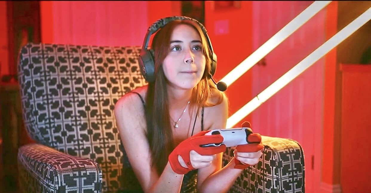 Woman wearing red SLEEKZ gloves while she play video games in a red room