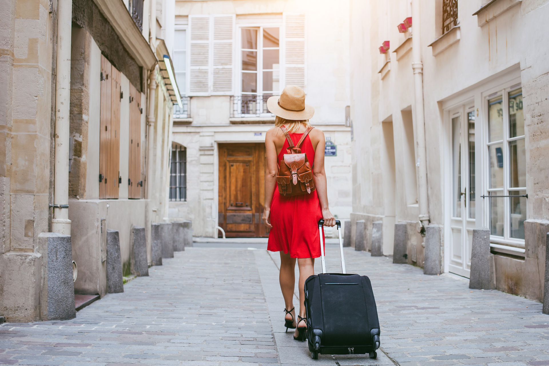 Woman in red dress and sun hat pulling her suitcase behind her as she walks into a hotel