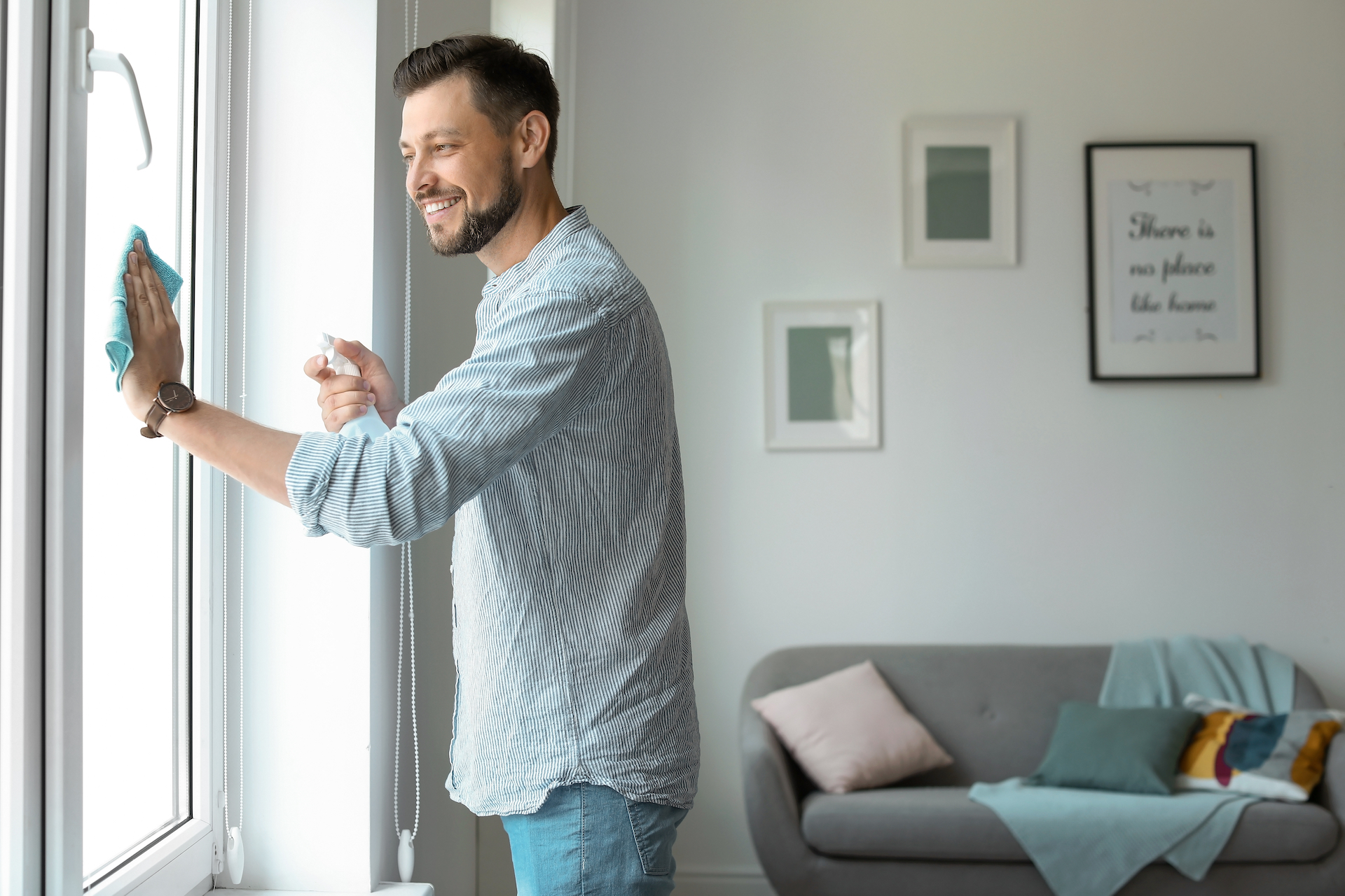 Man wiping glass window happily in his living room
