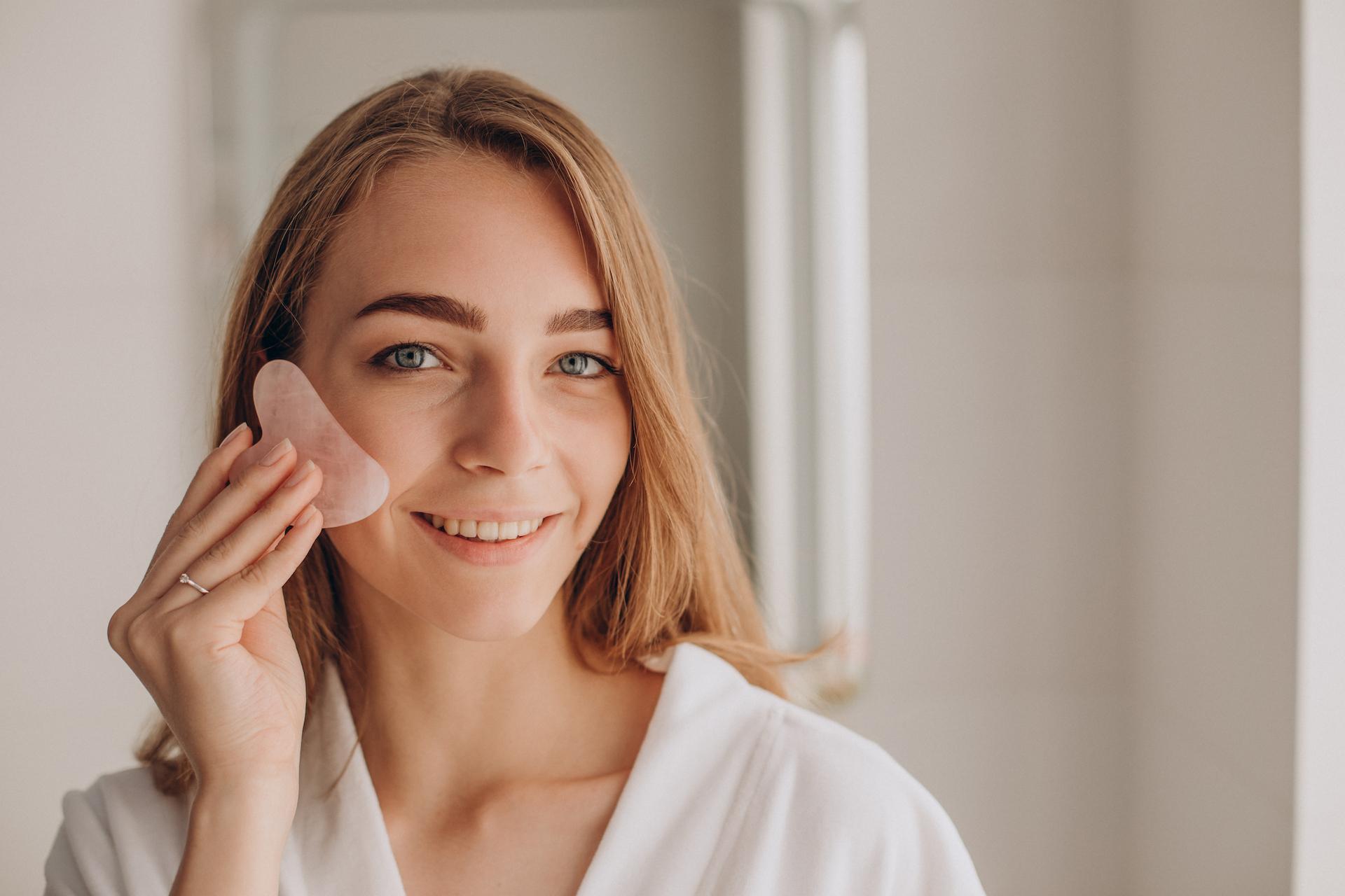 Woman holding a gua sha stone, getting ready for a gua sha facial
