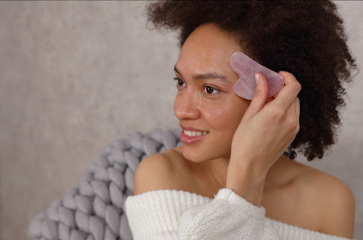 Woman using a gua sha stone to massage her face