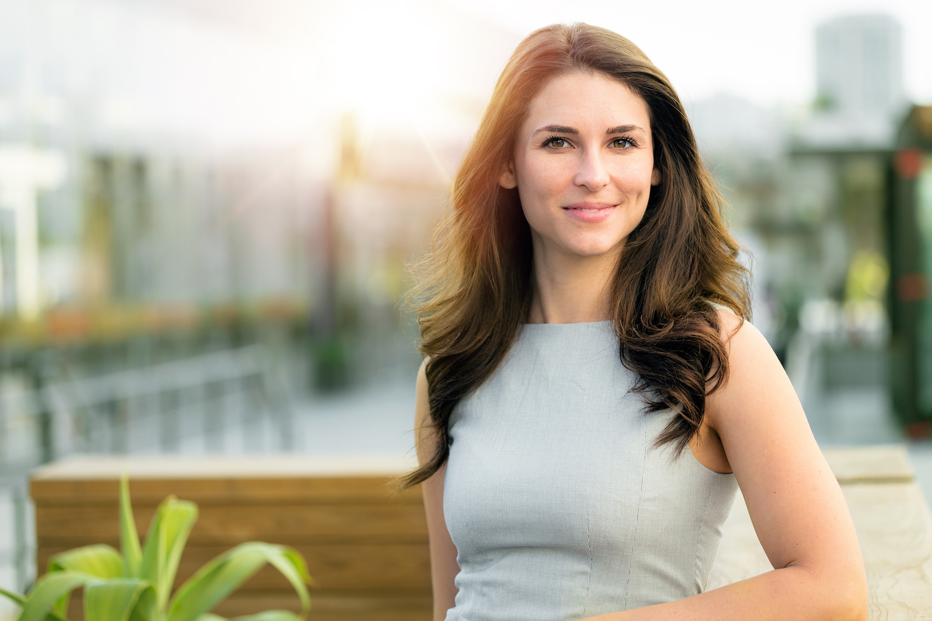 Woman with beautiful brown hair looking at the camera in front of a city