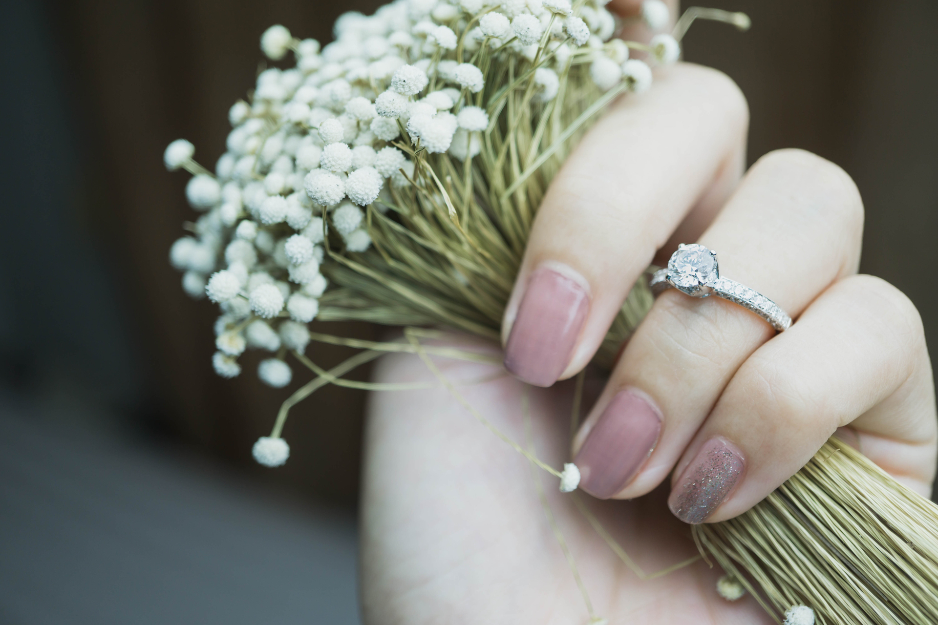 Close up of woman's hand holding flowers and wearing a lab grown diamond ring