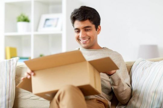 Man smiling while he opens a box on his couch