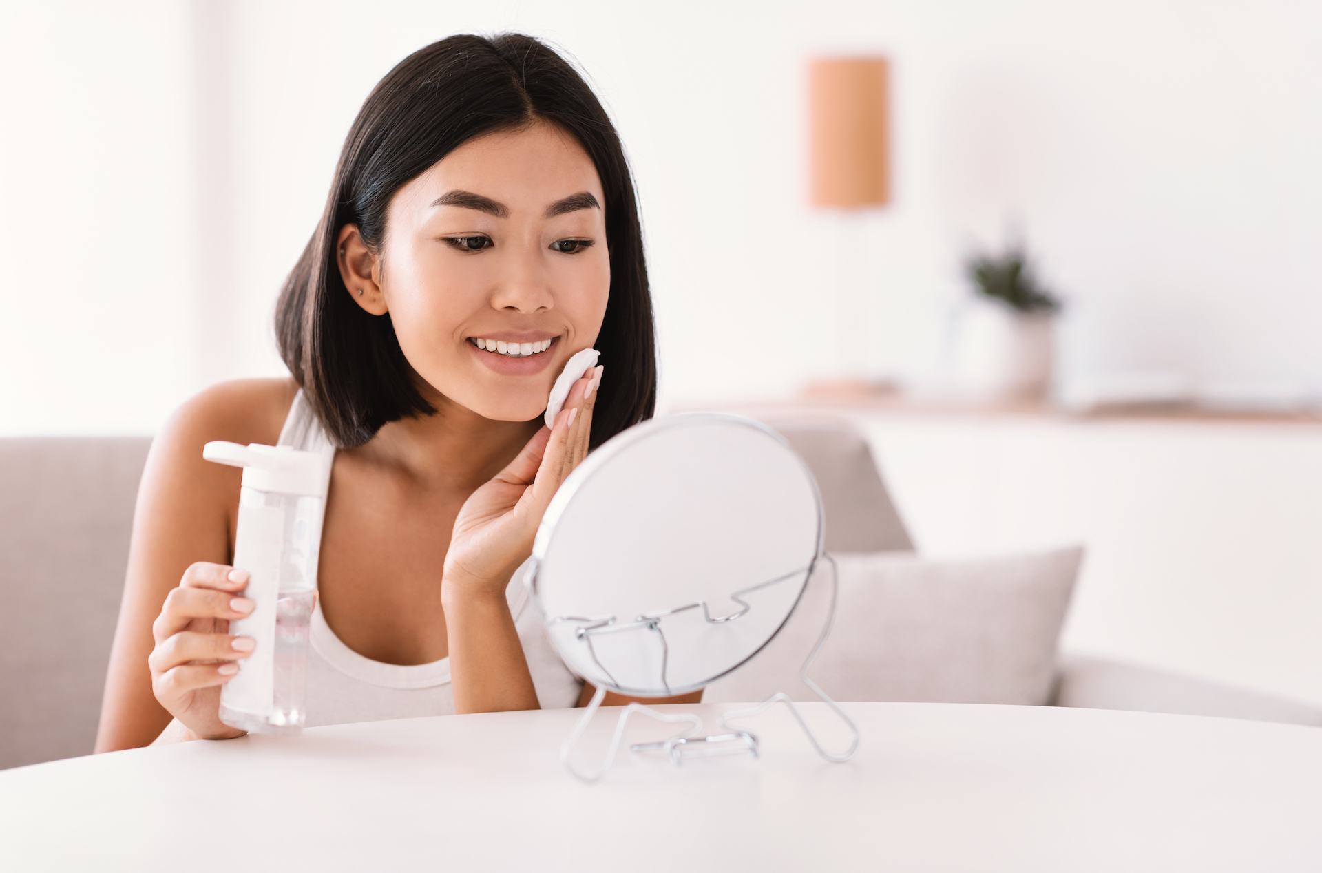 Woman putting micellar water on her face