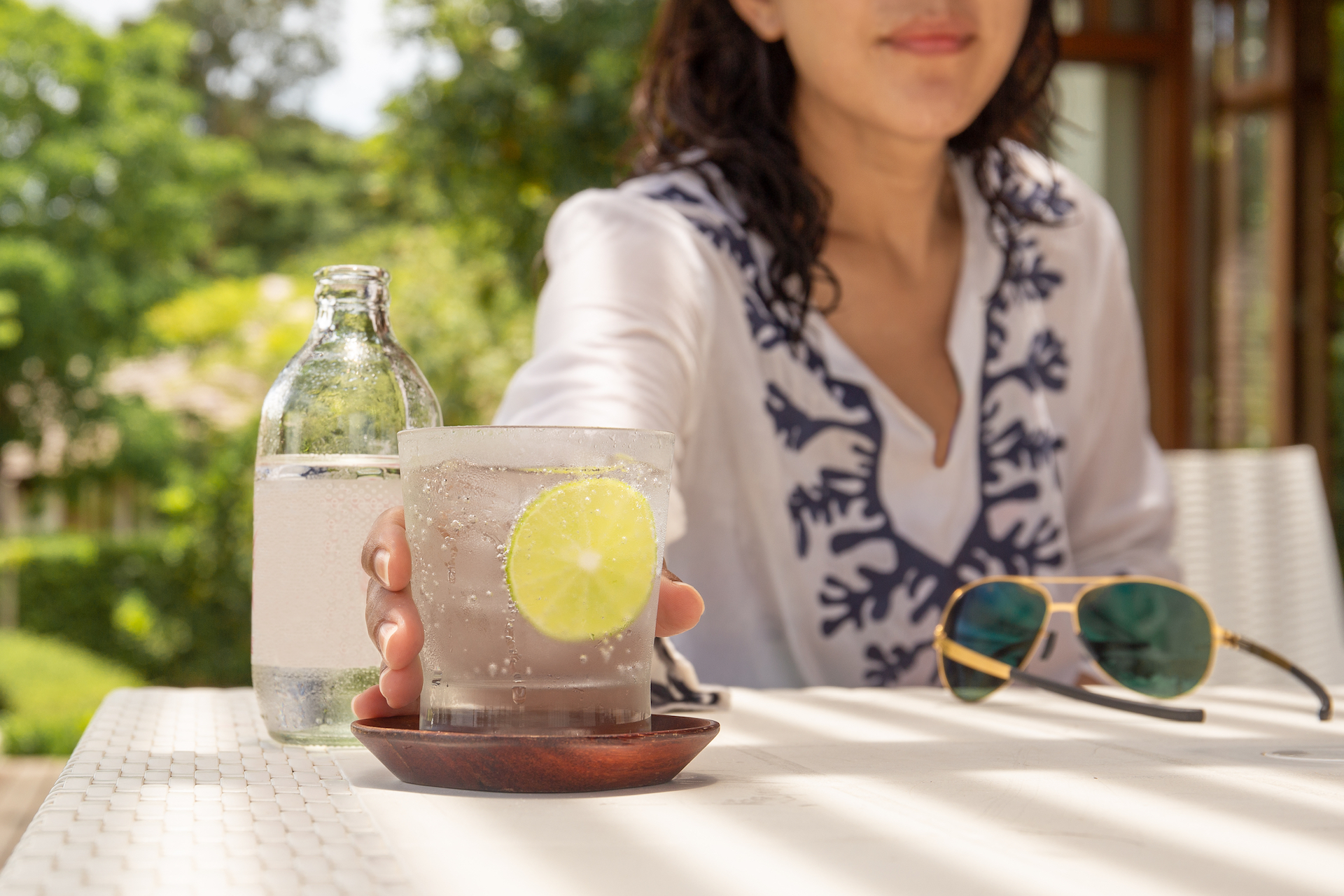 Woman holding a glass of sparkling prebiotic soda water in front of the camera