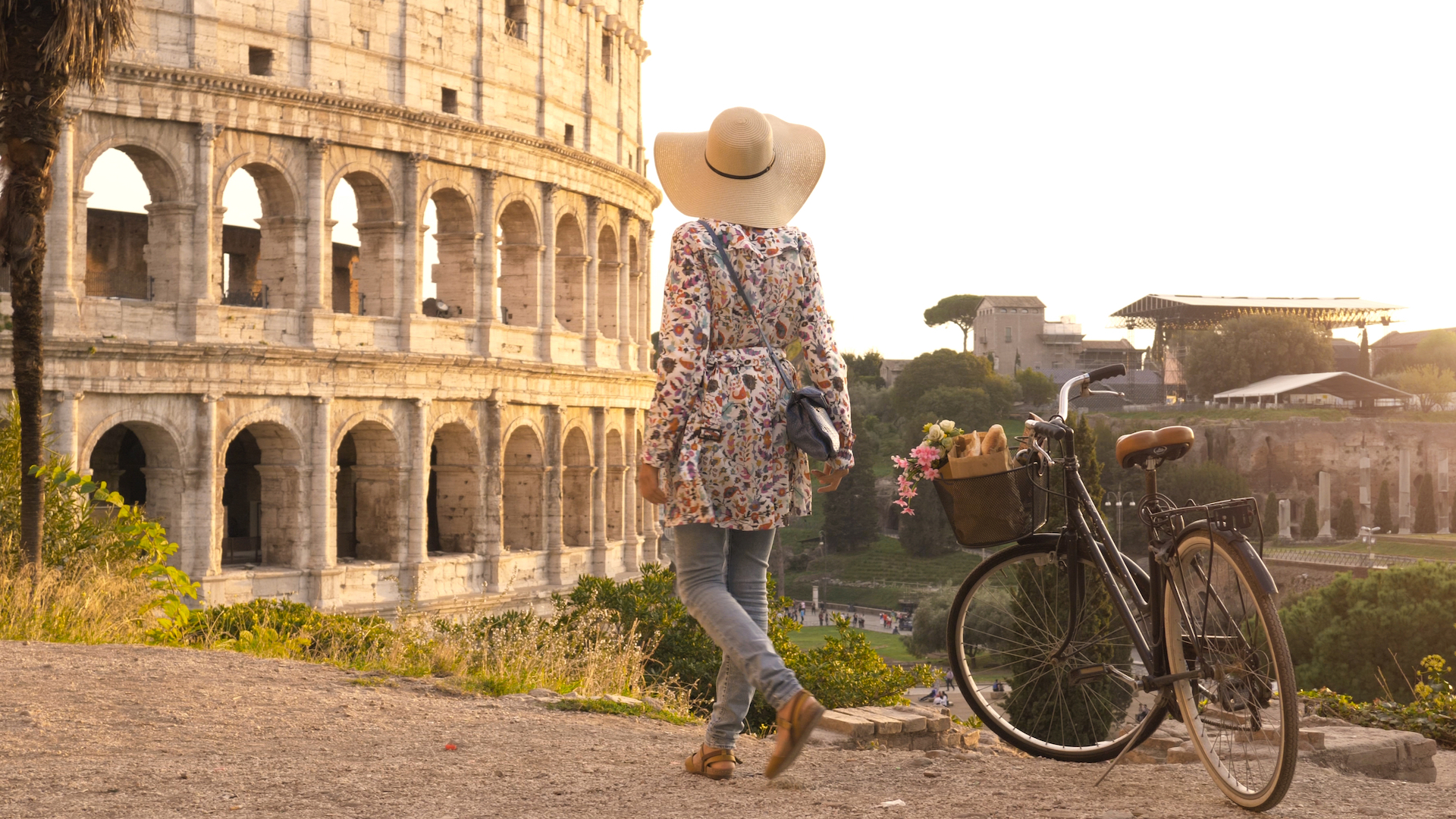 Woman walking away from her bike at the colosseum