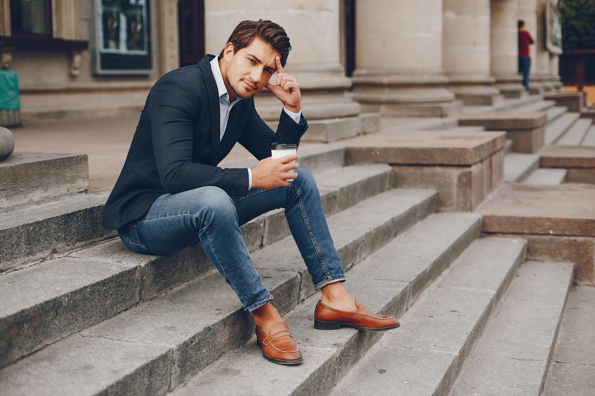 Stylish man in leather loafers and a sports coat drinking coffee on some cement steps