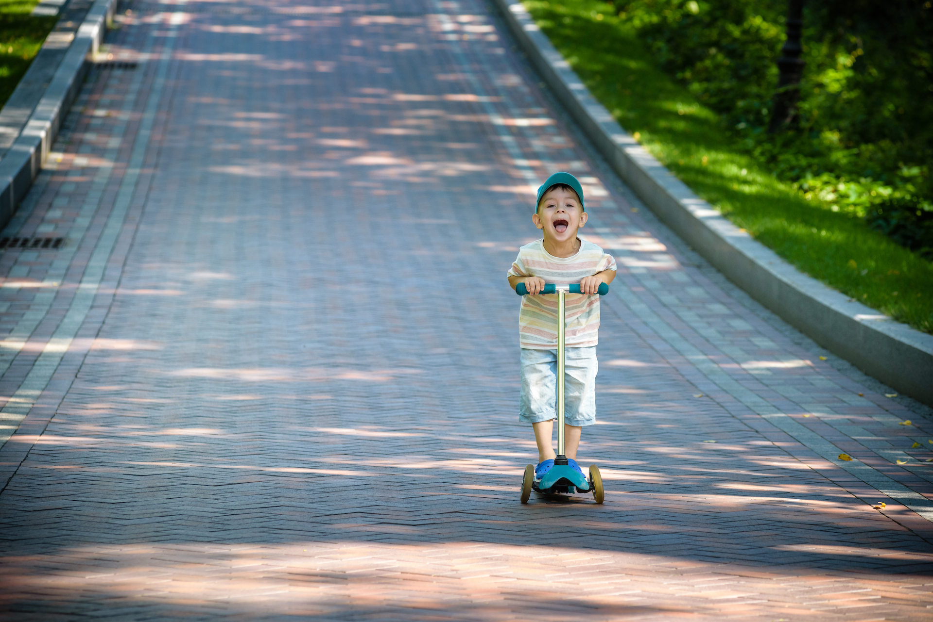Little boy riding down a hill on his three wheeled scooter