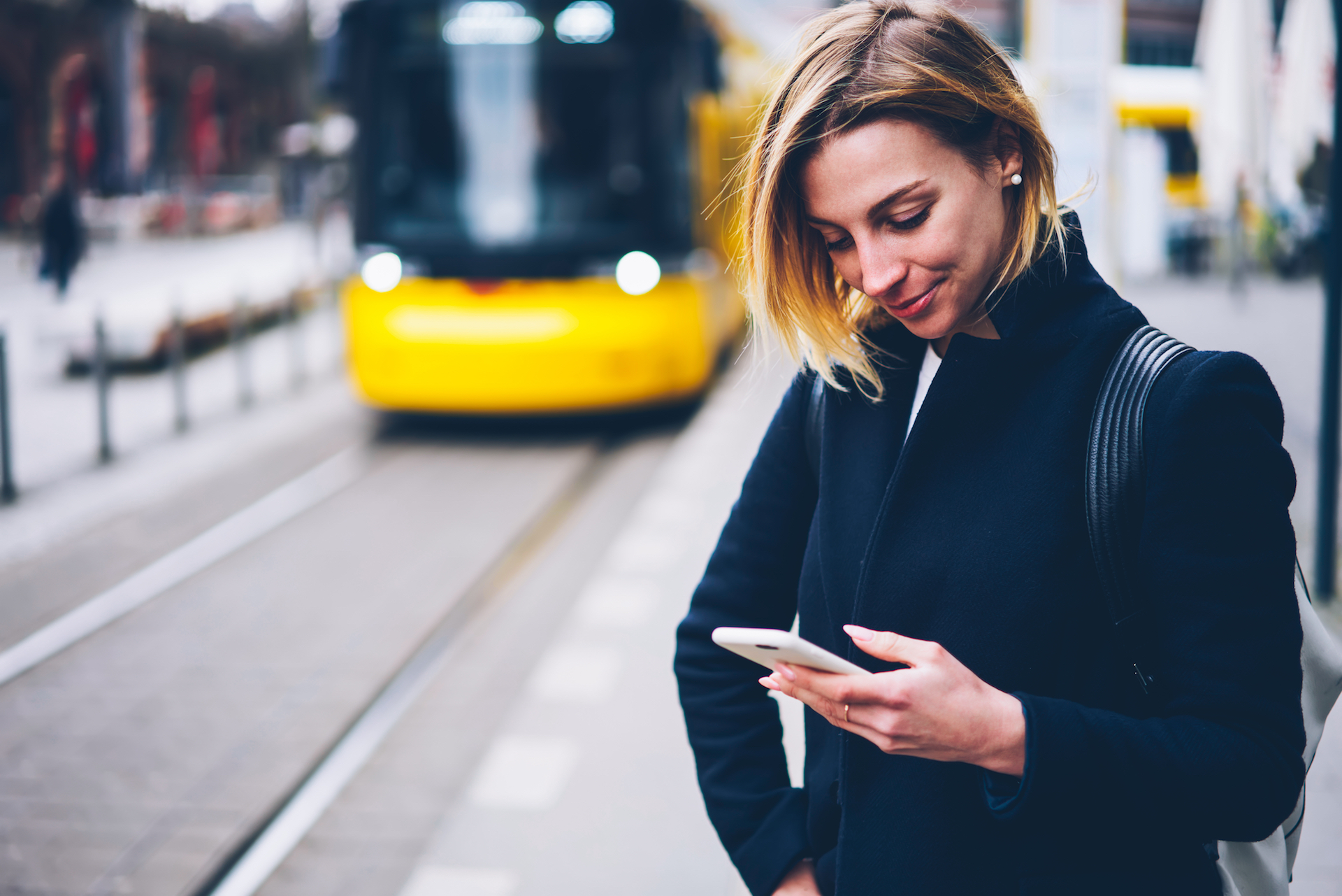 Woman looking at her phone while a city bus approaches in the background