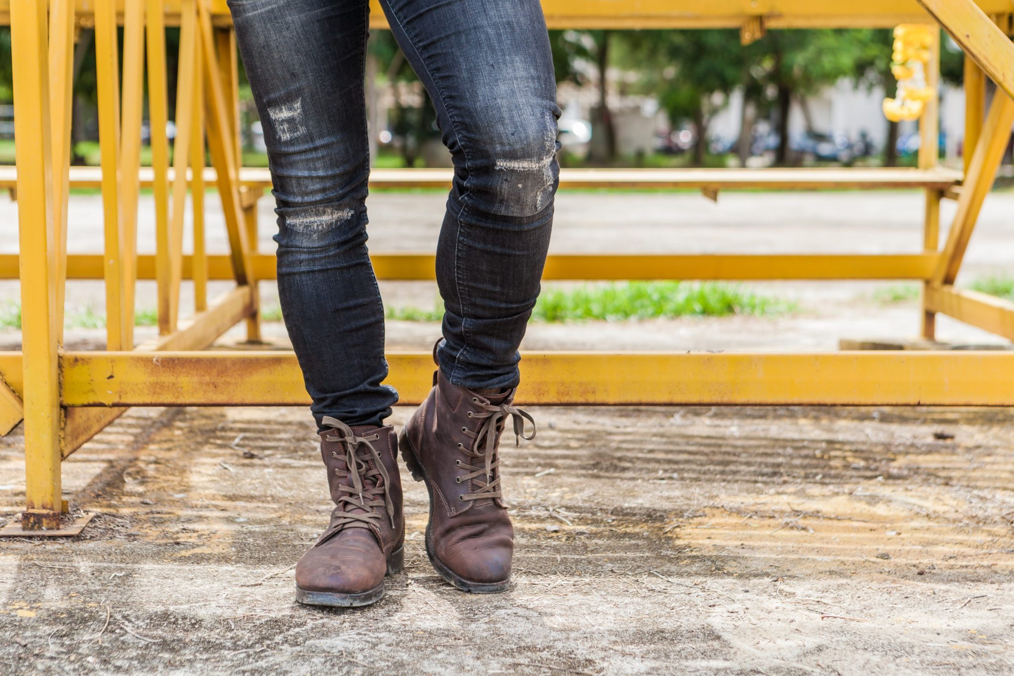 Someone standing with distressed skinny jeans and work boots in front of a yellow gate