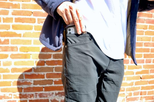 Man pulling out phone in Western Rise Evolution pants