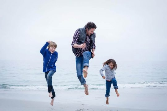 Man playing and jumping around with his kids on a windy beach