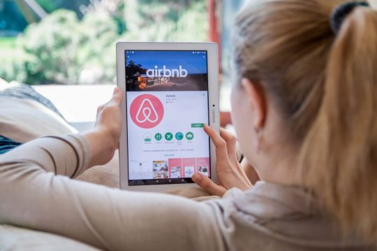Woman looking up airbnb on her tablet