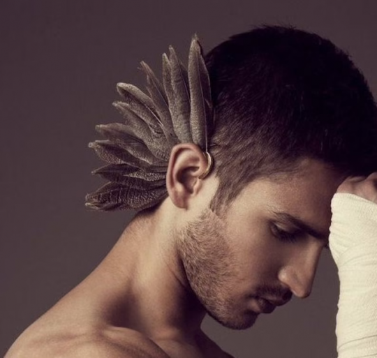 man with feather ear cuff