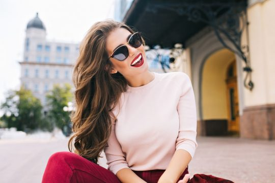 Woman sitting on the ground outside of a charming building, smiling at the camera  with her head tilted and bright red lipstick