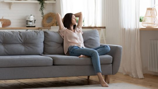 Woman relaxing on her couch in a clean house