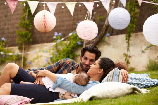 Man, woman and baby cuddling on the grass with blankets, pillows and floating lanterns