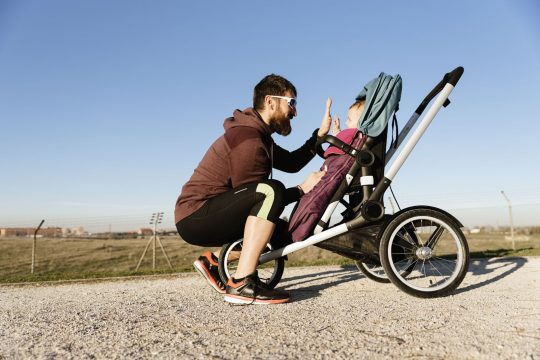 Man giving his baby a high five from the jogging stroller