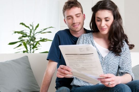 Man and woman looking at their utility bills