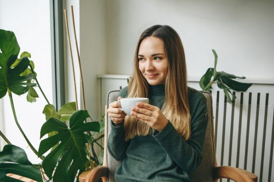 Woman drinking tea with some plants in the background