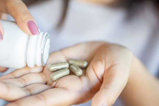 Woman pouring some pills into her hand