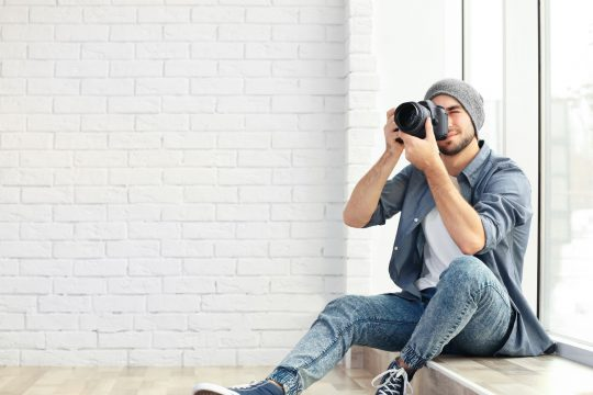 Man sitting on the ground taking a photo of a home