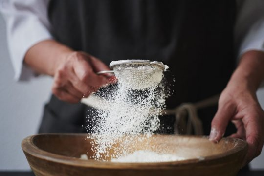 Man sifting tiger nut flour