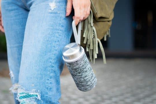 Woman holding a steel water bottle as she walks