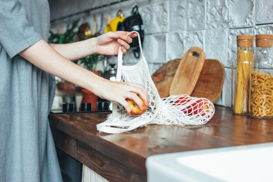 Woman taking produce out of her reusable mesh bags