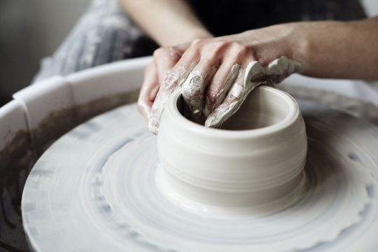 Woman throwing some pottery on a wheel