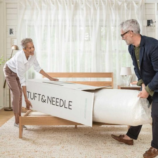 Man and woman taking a Tuft & Needle mattress in a box out