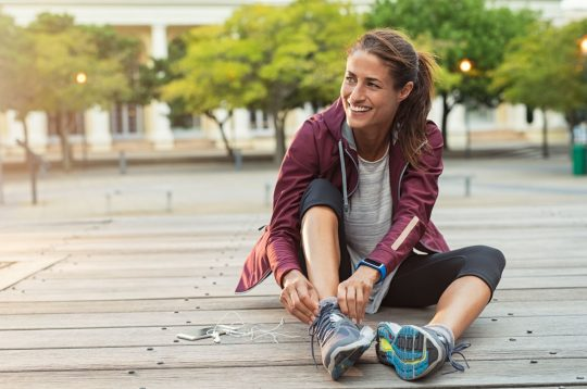 Woman tying her running shoes