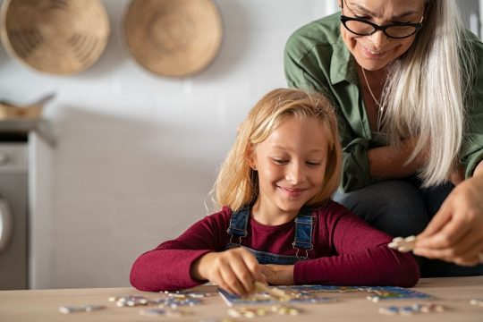 Woman and her granddaughter putting a puzzle together
