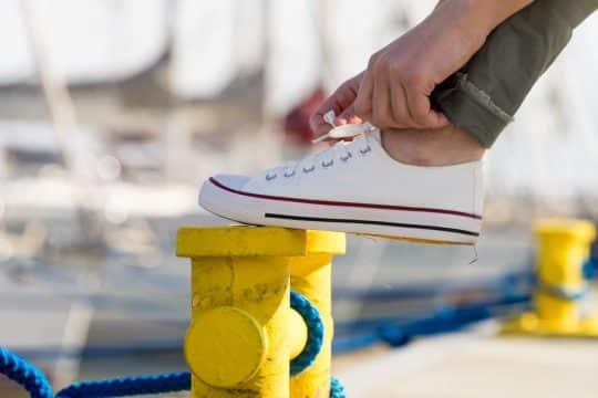 Woman tying her white sneaker on a dock