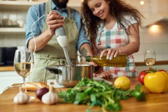 Man and woman cooking dinner with an immersion blender and a glass of wine nearby