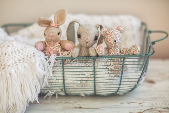 Three vintage stuffed bunnies in a greenish metal basket and a knitted white blanket