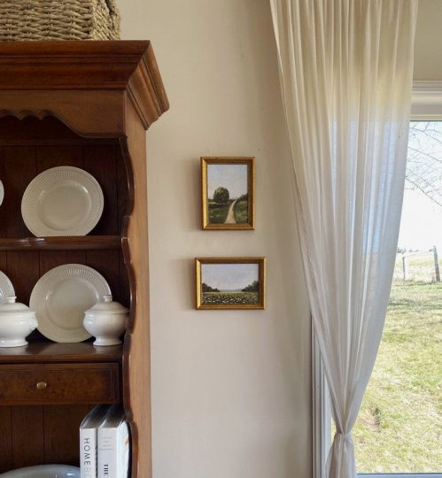 Two handmade pictures in gold frames hanging next to a wooden hutch