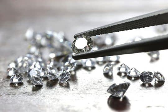 A closeup of tweezers holding diamonds