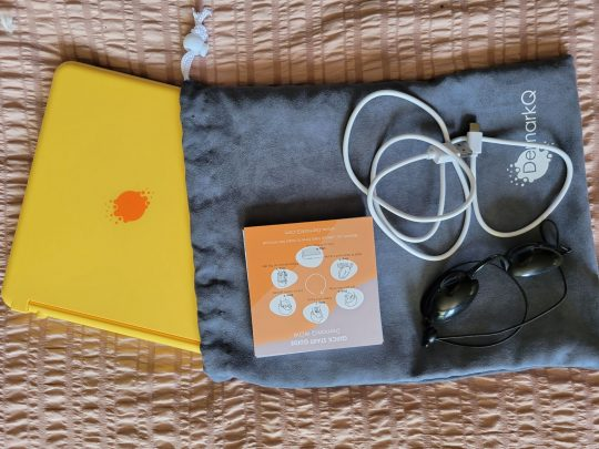 DemarkQ device, goggles, charging cord and grey fabric carrying case
