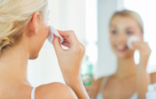 Woman putting toner on her skin