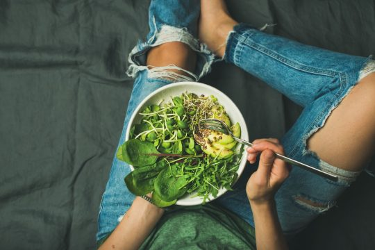 Woman eating some healthy greens from a bowl
